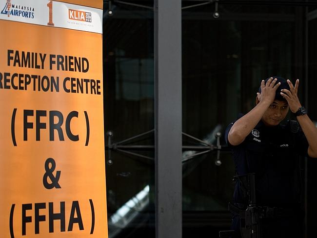 A Malaysian policeman stands guard outside a reception centre for family and friends at the Kuala Lumpur International Airport