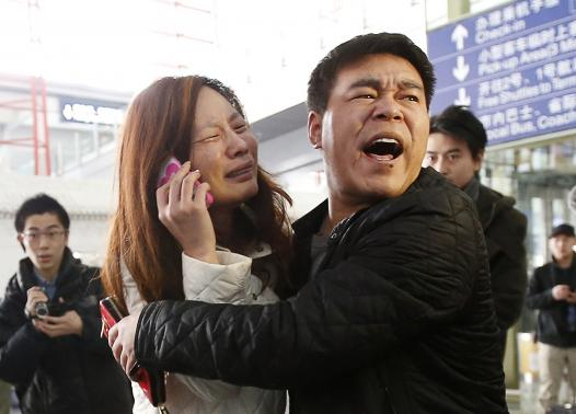 A relative (woman in white) of a passenger onboard Malaysia Airlines flight MH370 cries as she talks on her mobile phone at the Beijing Capital International Airport March 8, 2014.