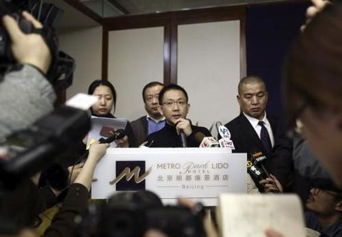 A Malaysia Airlines spokesman (C) speaks to journalists regarding information about Malaysia Airlines flight MH370, during a news conference at a hotel in Beijing March 8, 2014