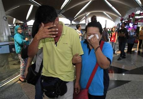 A woman wipes her tears after walking out of the reception center and holding area for family and friend of passengers aboard missing MH370