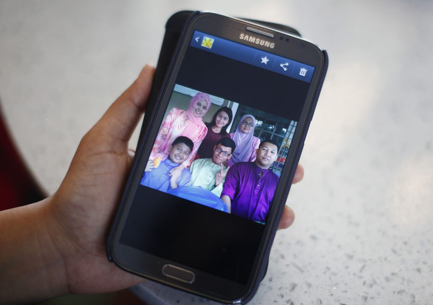 Arni Marlina, 36, a family member of a passenger onboard the missing Malaysia Airlines flight MH370, shows a family picture on her mobile phone, at a hotel in Putrajaya March 9, 2014