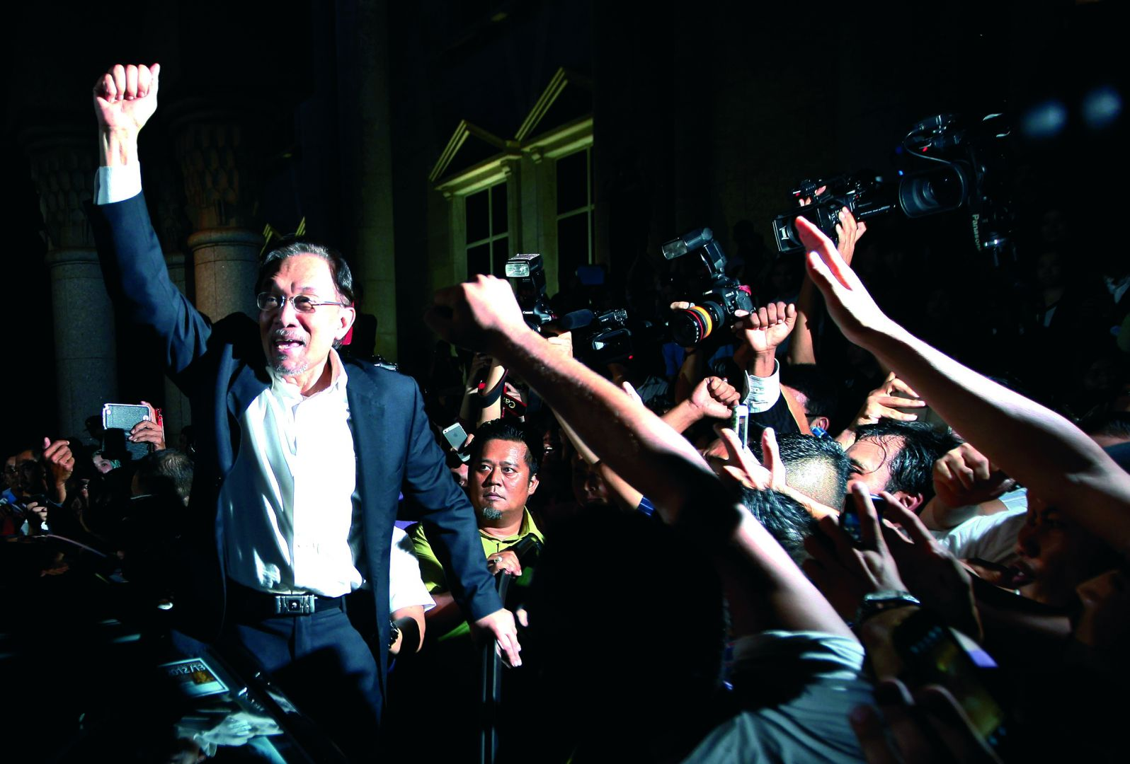 Malaysian opposition leader Anwar Ibrahim shouts to his supporters outside court yesterday. His lawyers won a stay of the sentence pending an appeal.
