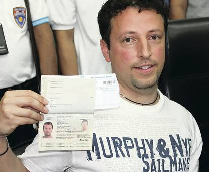 Italian Luigi Maraldi, left, whose stolen passport was used by a passenger boarding a missing Malaysian airliner, shows his passport as he reports himself to Thai police at Phuket police station in Phuket province, southern Thailand