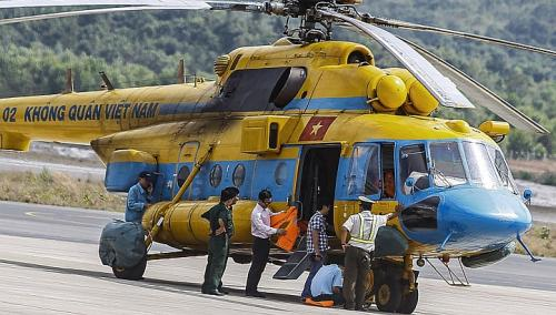 Vietnamese military personnel prepare a helicopter for a search and rescue mission for the missing Malaysia Airlines (MAS) flight MH370 off Vietnam's southern coastline, at a military base on the southern island of Phu Quoc on March 10, 2014.
