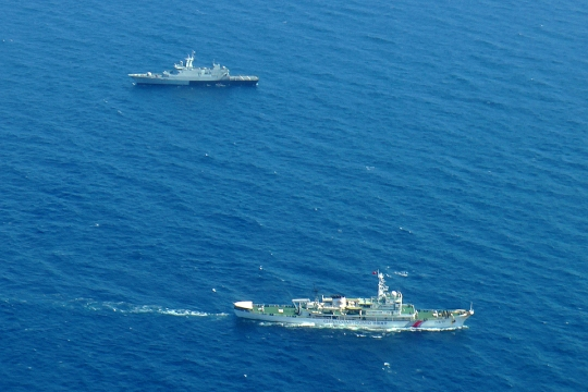 A Chinese coast guard (bottom) and a Malaysian navy ship patrolling the waters during search and rescue operations for the missing MH370 in the waters off the northeastern coast of the peninsula.
