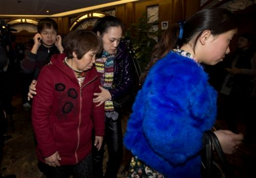 Chinese relatives of passengers aboard a missing Malaysia Airlines plane leave a hotel room after meeting with Malaysian officials, in Beijing, China Wednesday, March 12, 2014.