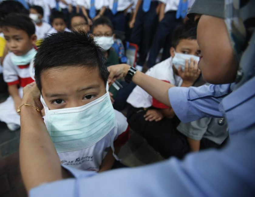 File pic of a teacher helping her student put on a face mask due to the haze
