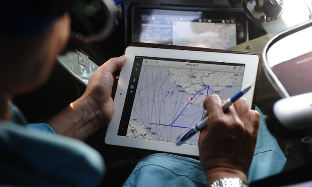 A pilot on a Vietnamese air force plane uses a map to help search Vietnam's southern sea for missing flight MH370. The hunt spread to the vast Indian Ocean after the White House cited 'new information' that it might have flown for hours after vanishing nearly seven days ago