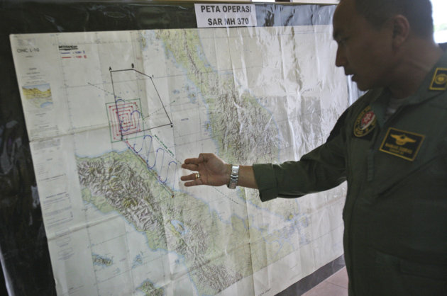 "Lt. Col Bambang Sudewo, commander of the 5th Air Squadron ""Black Mermaids"" examines a map following a search operation for the missing Malaysia Airlines Boeing 777 that was conducted over the Strait of Malacca, at Suwondo air base in Medan, North Sumatra, Indonesia"