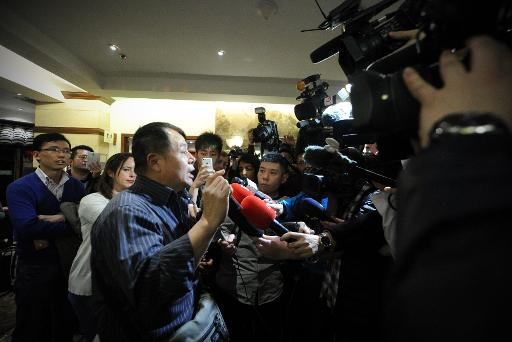 A relative (L) of passengers from the missing Malaysia Airlines flight MH370 speaks to media at a hotel in Beijing on March 15, 2014
