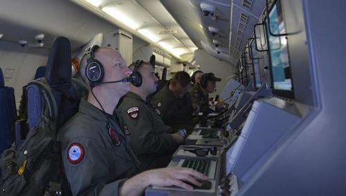Crew members on board a United States Navy P-8A Poseidon man their workstations while assisting in search operations for Malaysia Airlines flight MH370 over the Indian Ocean on March 16, 2014.