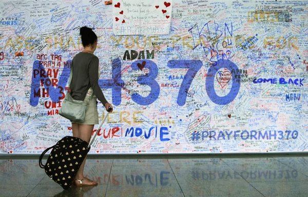 A woman looks at messages of support left for family members and passengers onboard the missing Malaysia Airlines Flight MH370 at the Kuala Lumpur International Airport (KLIA) in Sepang, outside Kuala Lumpur, on Tuesday.