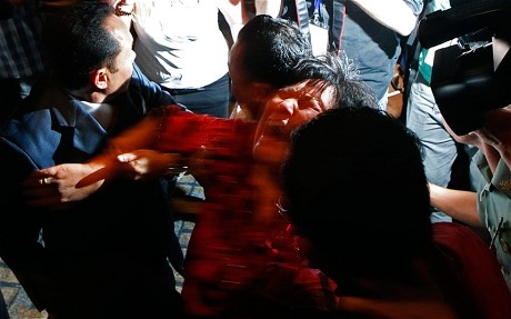 A Chinese family member of a passenger onboard MH370 screams as she is being brought into a room outside the media conference area at a hotel in Kuala Lumpur