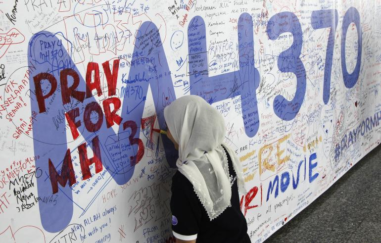 A woman writes on a banner of well wishes for the passengers of the missing Malaysia Airlines Flight MH370 at Kuala Lumpur International Airport