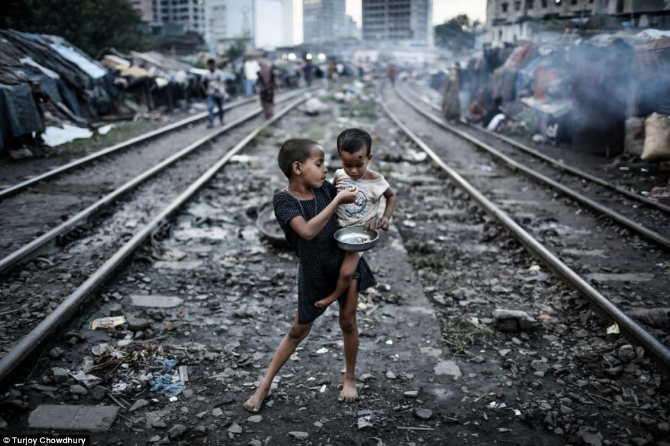 These two children eating tiny scraps of food on a railway in the slums of Bangladesh, shot by Turjoy Chowdhury, captured the hearts of the jury