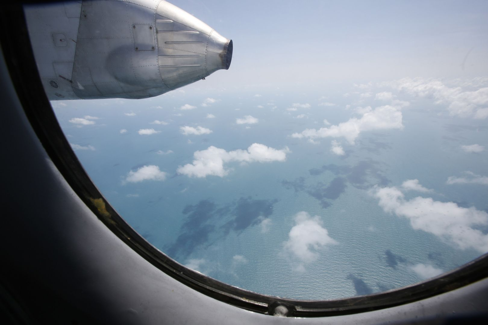 Clouds hover outside the window of a Vietnam Air Force search and rescue aircraft An-26, on a mission to find the missing Malaysia Airlines flight MH370