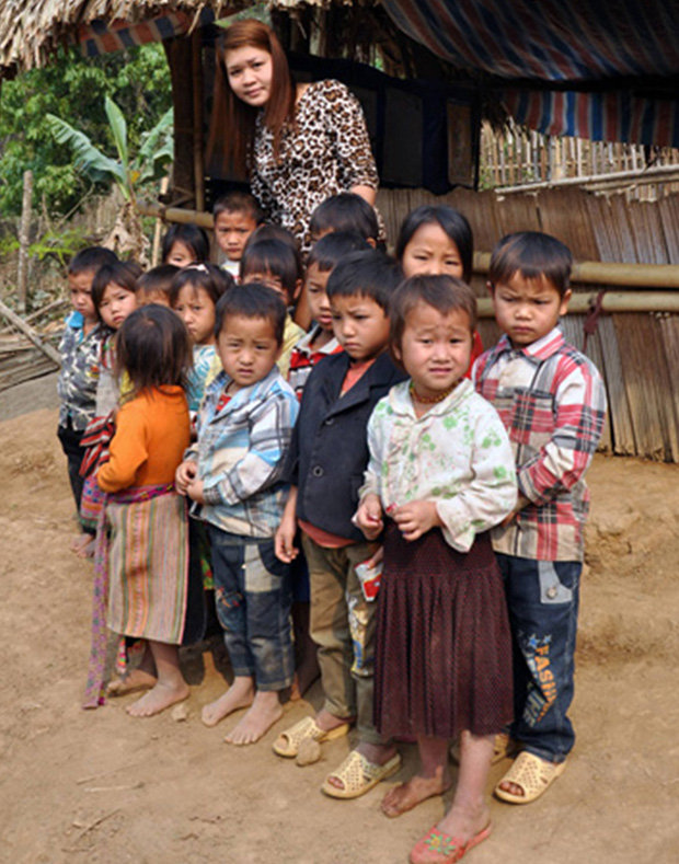 Teacher Tong Thi Minh pictured with the class who were taken across the river in bags