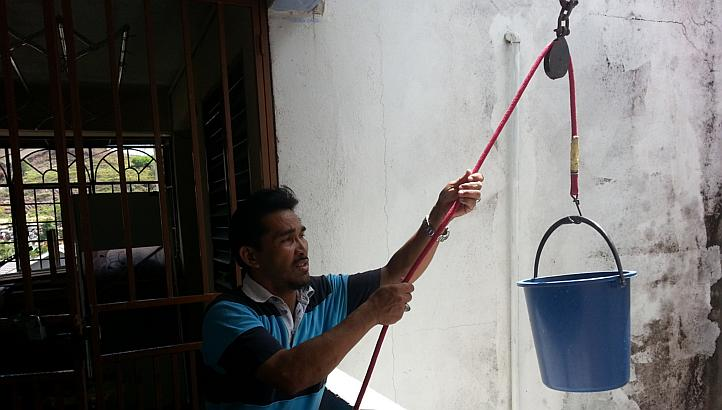 Contractor Rezuan Hussain demonstrating the pulley system he installed to make it easier to transport water in his apartment block in Balakong, Selangor.