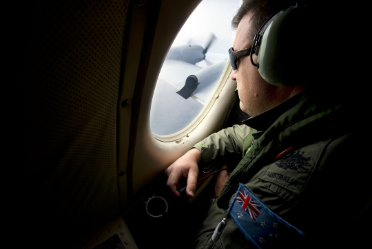 Royal Australian Air Force (RAAF) airborne electronics analyst Warrant Officer Nicholas Harding looks out from a AP-3C Orion as he flies over the southern Indian Ocean participating in the search for missing Malaysian Airlines Flight MH370
