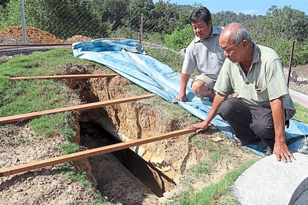 Disturbing find: Yau (right) and friend Loh Chew Lim, 53 inspecting the grave of his late mother that had been dug all the way down to the coffin at the cemetery in Kampung Gapis, Nyalas.