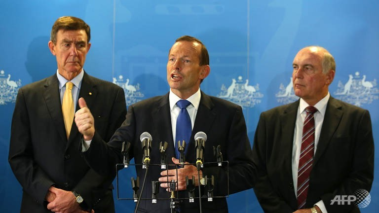 Australian Prime Minister Tony Abbott (C) addresses the media on Malaysia Airlines Flight MH370 together with former Defence Force Chief Angus Houston (L) and Deputy Prime Minister Warren Truss (R) at RAAF Base Pearce in Bullsbrook, Western Australia on Monday.