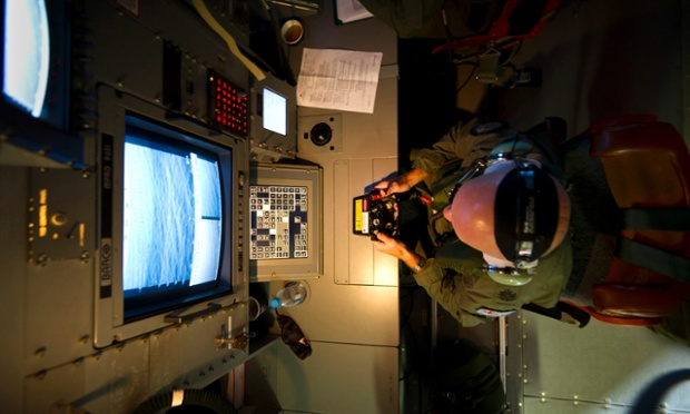 Royal Australian Air Force Warrant Officer Michael Wright uses the advanced optical systems aboard a RAAF AP-3C Orion aircraft during the search in the southern Indian Ocean for debris from the missing Malaysian Airlines flight MH370.
