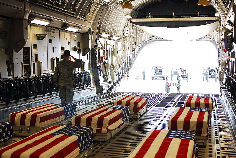 Transfer cases containing the remains of soldiers killed in the shooting being loaded aboard an aircraft for flight to Dover Air Force Base