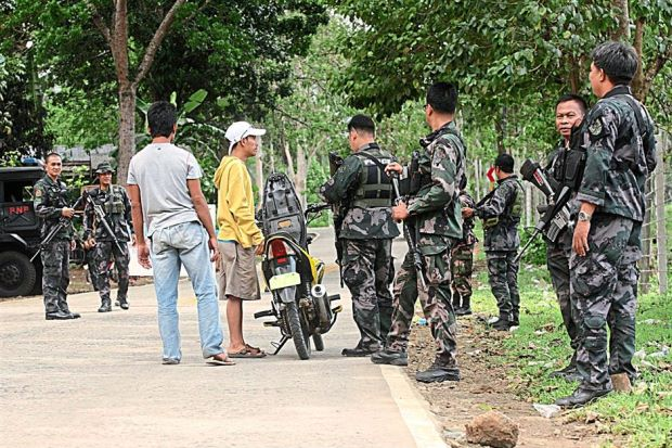Members of the Philippine National Police (PNP) 52nd Special Action Company conducting a security check on motorists at a checkpoint in Indanan Village, Sulu province in the Southern Philippines