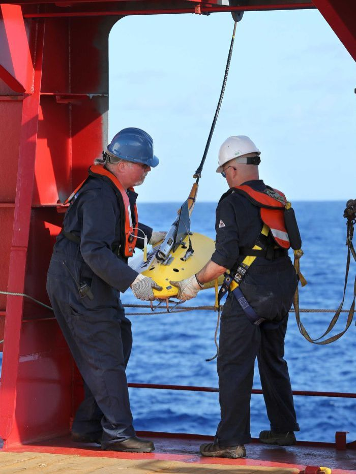 Phoenix Internaional personnel, Mike Unzicker and Chris Minor, deploy the towed pinger locator off the deck of Australian Defence Vessel Ocean Shield in the first search for the missing flight data recorder and cockpit voice recorder of Malaysia Airlines flight MH370, April 5, 2014.