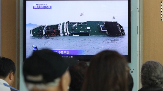 People watch a TV news program showing the sinking passenger ship at Seoul Railway Station.