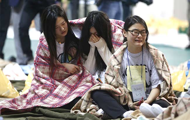 Rescued passengers cry at a gym where they gathered in Jindo