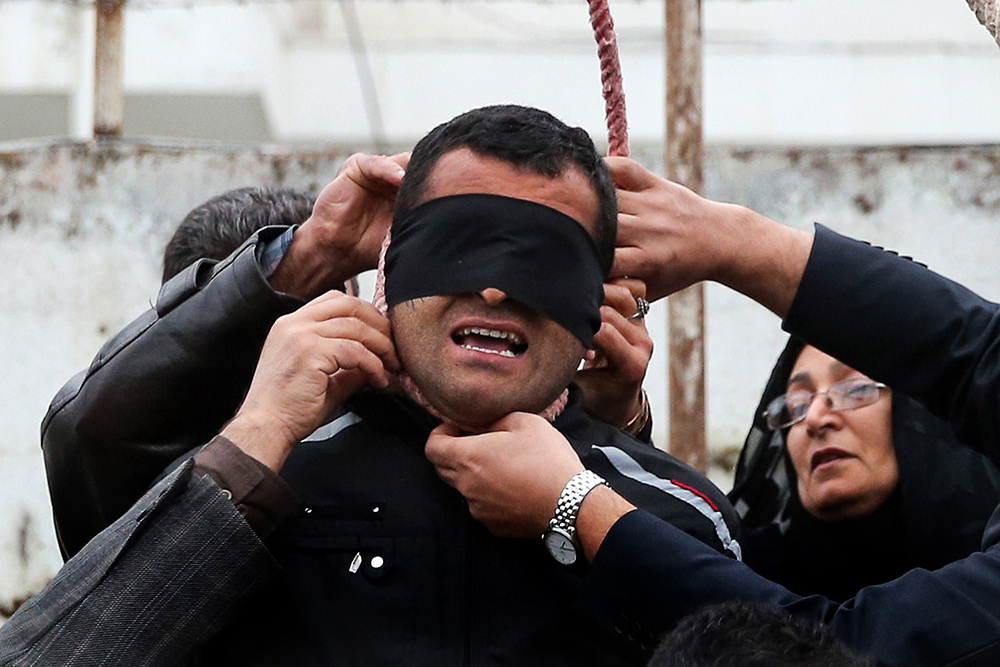 The mother of Abdolah Hosseinzadeh removes the noose with the help of her husband from around the neck of Balal, sparing the life of her son's convicted murderer, April 15, 2014.