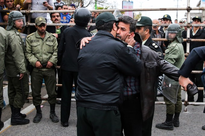 A police office kisses Abdolghani Hosseinzadeh (C-R) the father of Abdolah Hosseinzadeh who was killed by a fellow Iranian, named Balal, in a street fight with a knife in 2007, during Balal's execution ceremony in the northern city of Nowshahr on April 15, 2014.
