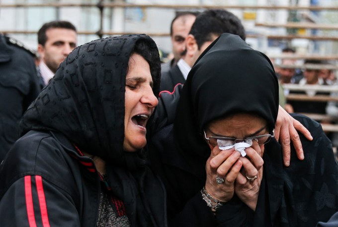 The mother of an Iranian man Balal, left, who killed an Iranian youth Abdolah Hosseinzadeh in a street fight with a knife in 2007, cries with the mother of Abdolah Hosseinzadeh after she forgave Balal, giving him an emotional slap prior to removing the noose around his neck in the gallows during his execution ceremony in the northern city of Nowshahr on April 15, 2014.