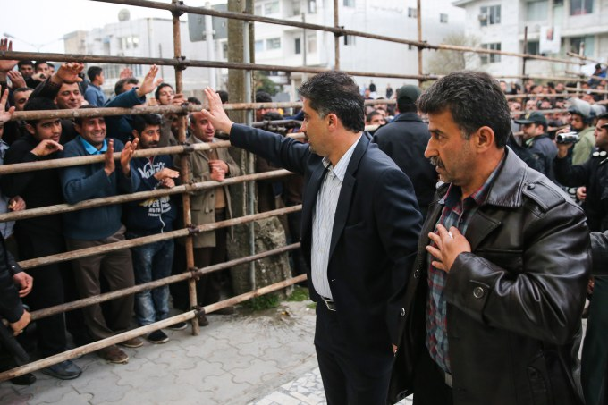 Bystanders applaud Abdolghani Hosseinzadeh (R) the father of Abdolah, an Iranian youth killed by fellow national Balal in a street fight with a knife in 2007, after he and his wife pardoned their son's convicted murderer, during his execution ceremony in the northern city of Nowshahr on April 15, 2014.