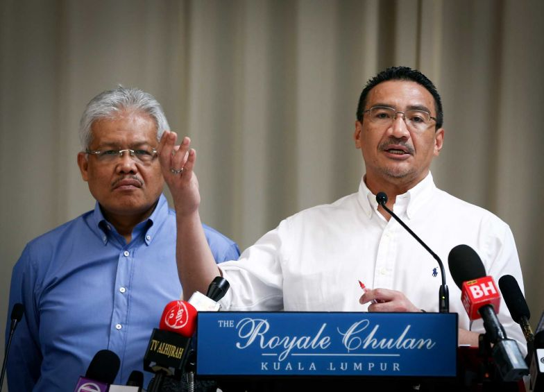 Malaysian Deputy Minister of Foreign Affairs Hamzah Zainudin, left, listens as Malaysia's acting Transport Minister Hishammuddin Hussein answers a question from a journalist during a press conference on the missing Malaysia Airlines Flight 370 at a hotel in Kuala Lumpur, Malaysia, Saturday, April 19, 2014.
