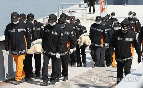 Police officers carry bodies of victims from the sunken ferry Sewol on April 20.