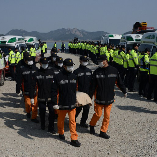 Rescue workers carry the body of a victim from the sunken South Korean ferry 'Sewol' at Jindo harbour on Sunday, April 20, 2014