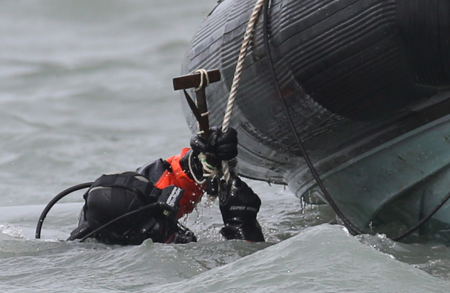 A diver carrying a hammer enters the water to search for missing passengers of the sunken Sewol off the coast of Jindo Island, South Jeolla Province, Tuesday.