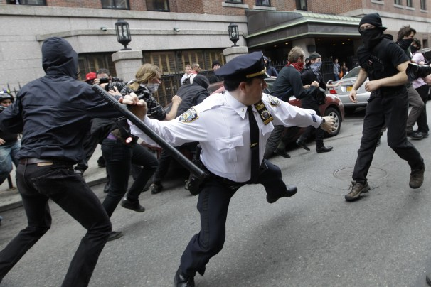 This file photo, from May 2012, shows a police lieutenant swinging his baton at Occupy Wall Street activists in New York. It was recirculated Tuesday in response to a police hashtag that went awry.