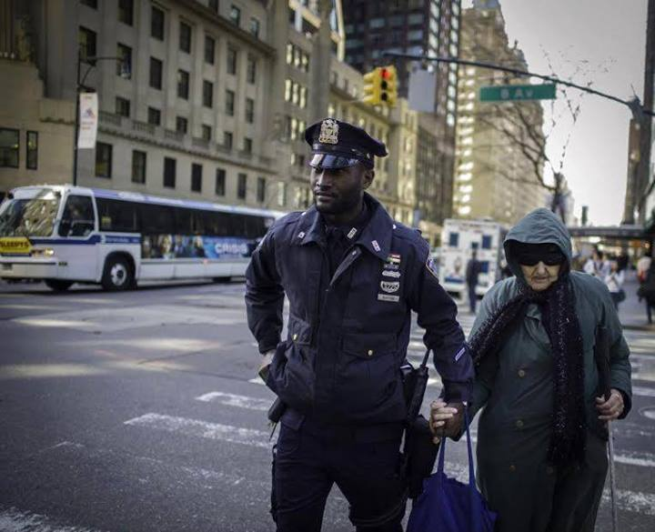 This photo, captured by a passerby and sent to the #NYPD, was taken as the police officer walked the woman two blocks to her destination.