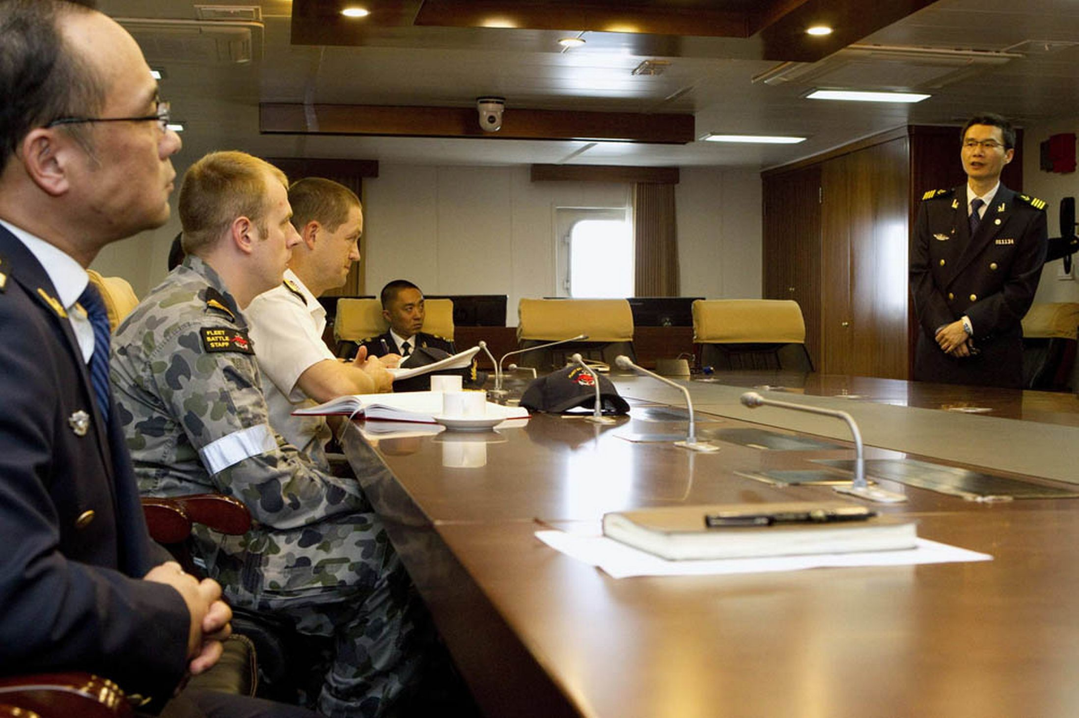 Commanding Officer of the Chinese Coast Guard vessel Haixun 01, Captain Jiang Long, gives a briefing to Senior Colonel Ma Liedong, Australian Navy Staff Officer Sub-Lieutenant Phillip Wagner, and Commander of Joint Task Force 658, Commodore Peter Leavy, (L-R) about the continuing search for the missing Malaysian Airlines flight MH370