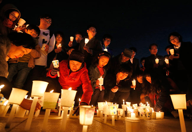 People attend a candlelight vigil in Ansan, to commemorate the victims of capsized passenger ship Sewol and to wish for the safe return of its missing passengers