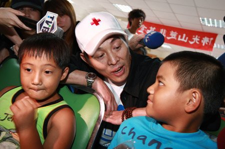 Chinese actor Jet Li (C) sings a song with children at a shelter in Chishan Town of Kaohsiung in southeast China's Taiwan, Aug. 15, 2009.