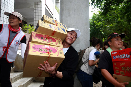 Chinese actor Jet Li (2nd L front) carries relief goods with volunteers in Liukuei Town of Kaohsiung in southeast China's Taiwan, Aug. 15, 2009.