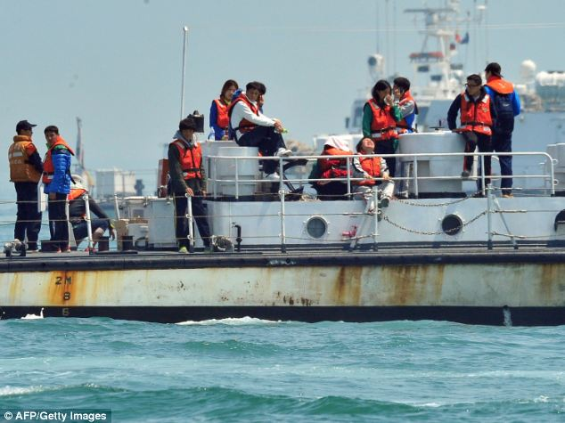 Relatives onboard a ship visit the site of the sunken South Korean ferry 'Sewol' on Thursday