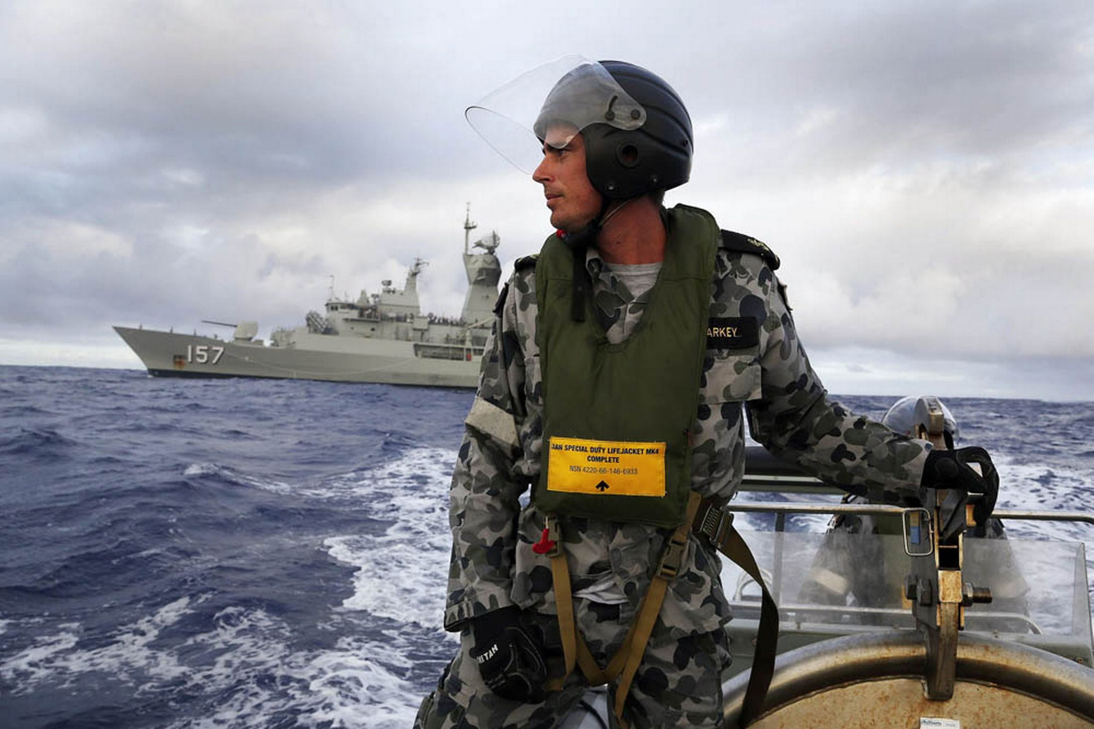 Standing in a rigid hull inflatable boat launched from the Australian Navy ship HMAS Perth, Leading Seaman, Boatswain's Mate, William Sharkey searches for possible debris in the southern Indian Ocean in the continuing search for the missing Malaysian Airlines flight MH370