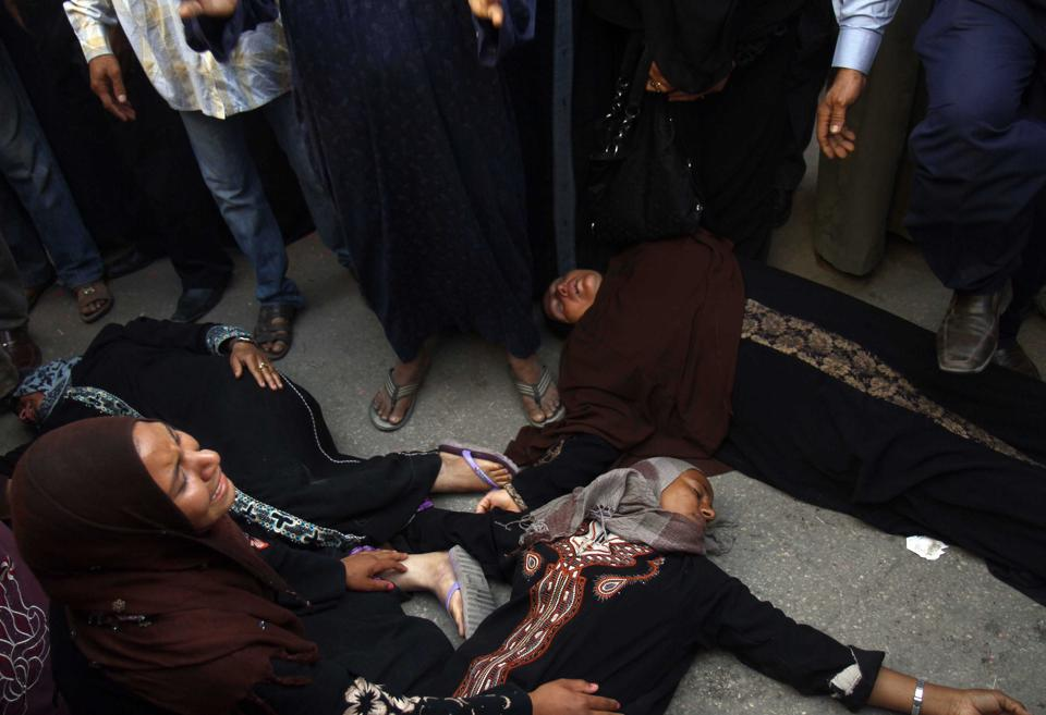 Egyptian women overcome by emotion fall to the ground after a judge sentenced to death more than 680 alleged supporters of the country's ousted Islamist president over acts of violence and the murder of policemen in the latest mass trial in the southern city of Minya, Egypt, Monday, April 28, 2014.