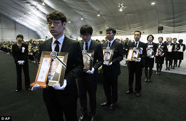 Mourners carry portraits of victims of the sunken ferry Sewol
