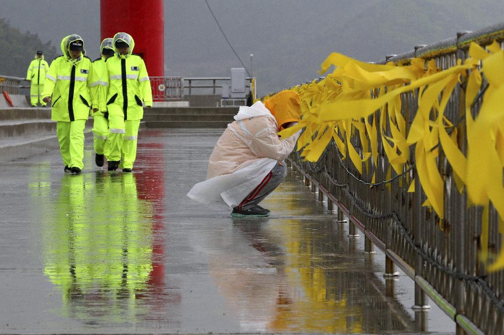 A relative of a passenger aboard the sunken Sewol ferry weeps as she awaits news on her missing loved one at a port in Jindo, South Korea, Sunday, April 27